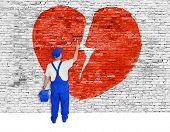 picture of love hurts  - Symbol of broken love painted over white brick wall by man - JPG