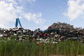 pic of junk-yard  - Scrap yard with crushed cars and blue sky  - JPG