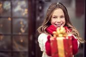 stock photo of cold-weather  - Child giving a Christmas present near her house door - JPG