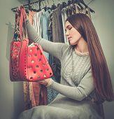 foto of showrooms  - Woman choosing bag in s showroom  - JPG