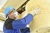 picture of glass-wool  - Man holding glasswool rolls in new built house - JPG