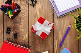 stock photo of office romance  - Red gift box and office supplies over office table - JPG