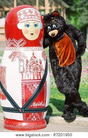 MOSCOW - MAY 12, 2014: actor dressed as bear hugs huge matryoshka in Sokholniki Park