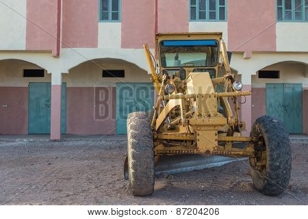 The Yellow Bulldozer Park In Front Of Colorful Building
