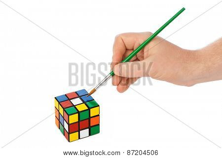 MOSCOW, RUSSIA - JANUARY 09, 2015: Hand with paintbrush and Rubik's cube puzzle isolated on the white background.