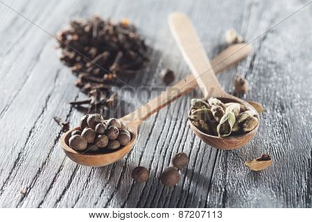 Nutmeg, clove and allspice in old spoon on wooden background. Natural raw image