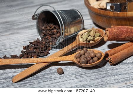Cardamon, clove and pepper in spoons on wooden background with various spices - cinnamon, ginger and nutmeg