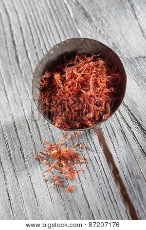 saffron in old spoon on wooden background