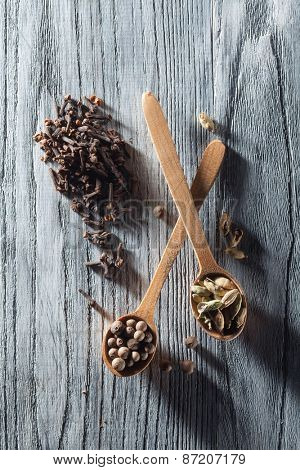 Nutmeg, clove and allspice in old spoon on wooden background with long shadows dramatic contrast light