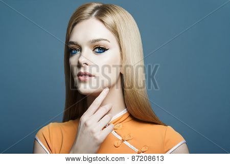 Portrait Of A Beautiful Blonde Girl In The Studio On A Blue Background, The Concept Of beauty
