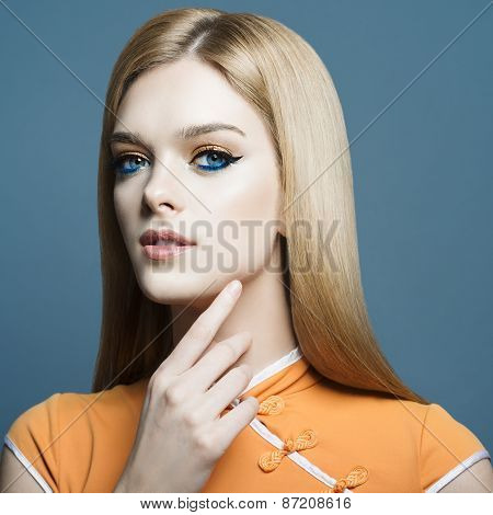 Portrait Of A Beautiful Young Blonde Girl In The Studio On A Blue Background, The Concept Of Health