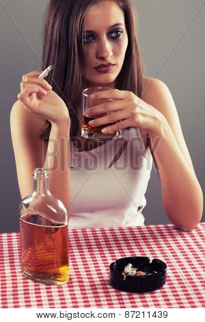 Sad woman drinking alcohol and smoking a cigarette