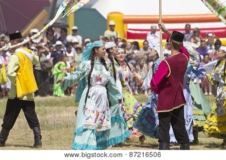 Men and women in national costumes dance traditional folk dances