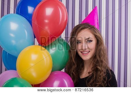 Smiling woman with birthday hat and colourful balloons