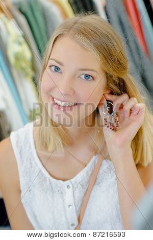 Woman trying on a pair of earrings