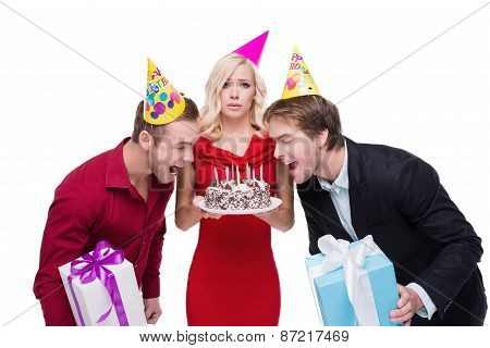 Funny people with birthday hats and cake