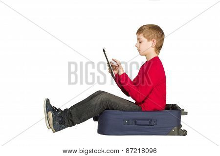 Boy Sitting In Travel Bag Using Tablet Isolated On White