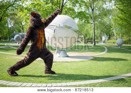 actor dressed as bear aerobics near sculptural model of solar system