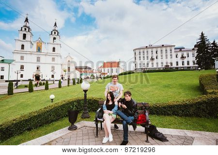 People resting, sitting on bench in park near The Cathedral Of H