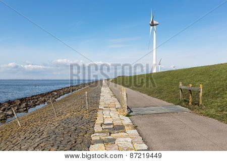 Dutch Coastline With Dike And Wind Turbines