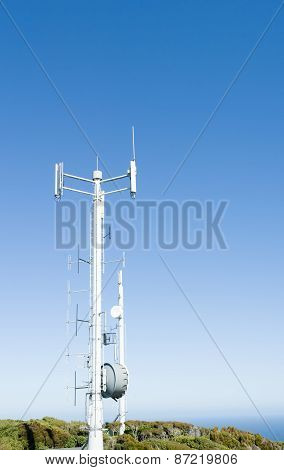 Mobile Communications tower on Bluff Hill, South Island, New Zealand stands against clear blue sky.