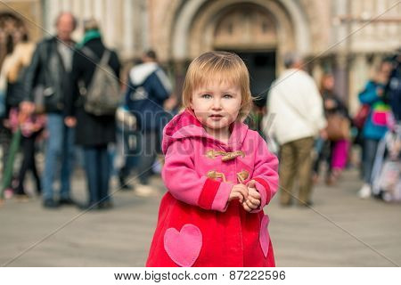 cute little girl walking on the Piazza San Marco in Venice, Italy