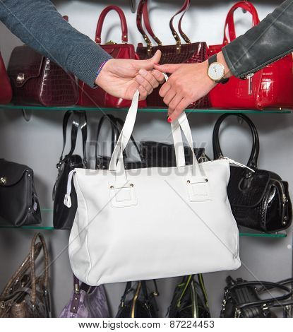 Shop Assistant Showing White Leather Bag To Woman