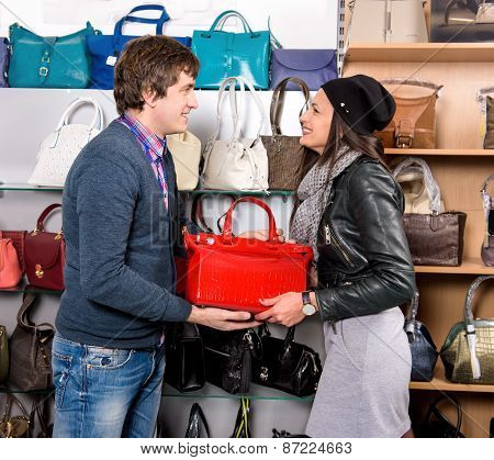 Shop Assistant Showing Red White Leather Bag To Beautiful Girl