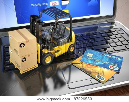 Concept of delivering, shipping or logistics. Forklift on laptop keyboard and credit cards. 3d