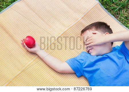 Boy Looking At Apple And Covering Eye By Hand