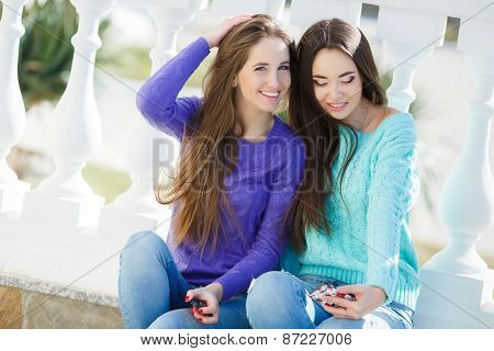 Two beautiful girlfriends watching pictures and listening to music on their smartphones.
