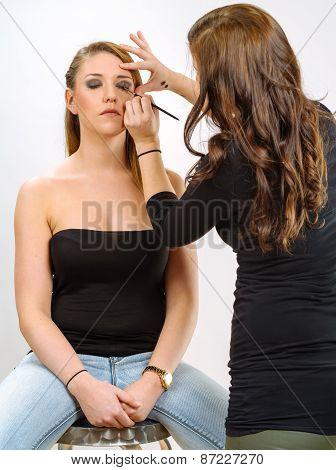 Applying Eye Makeup On Beautiful Model