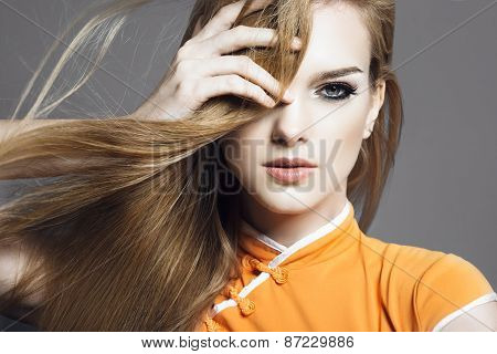 Portrait Of A Beautiful Blonde Girl In The Studio On A Gray Background With Developing Hair