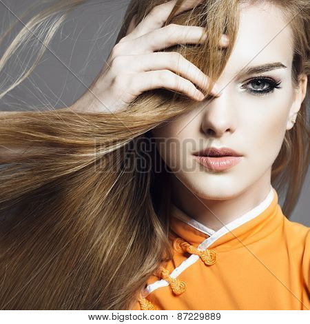 Portrait Of A Beautiful Young Blonde Girl In The Studio On A Gray Background With Developing Hair