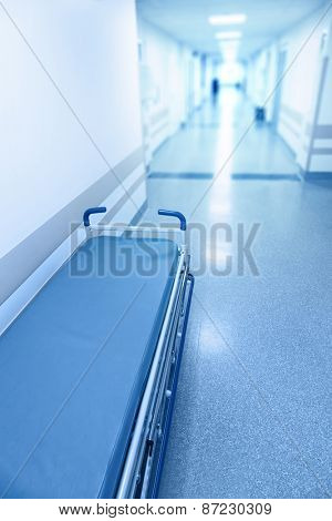 Long corridor in hospital with surgical gurney. Tinted picture