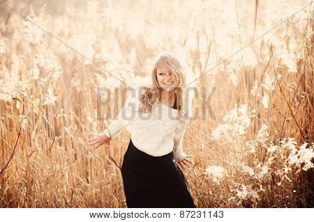 Portrait Of A Beautiful Young Blonde Girl In A Field In White Pullover, Laughing