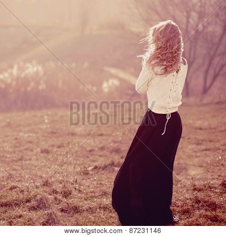Portrait Of A Beautiful Blonde Girl In The White Pullovers, Standing With His Back