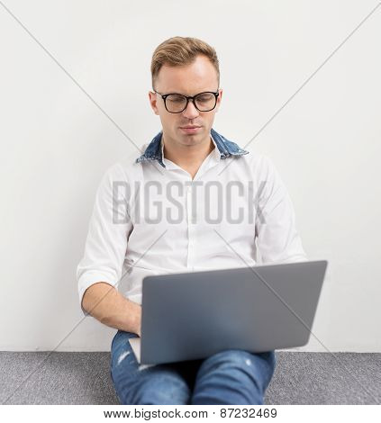 Young hipster using laptop computer while sitting on floor.