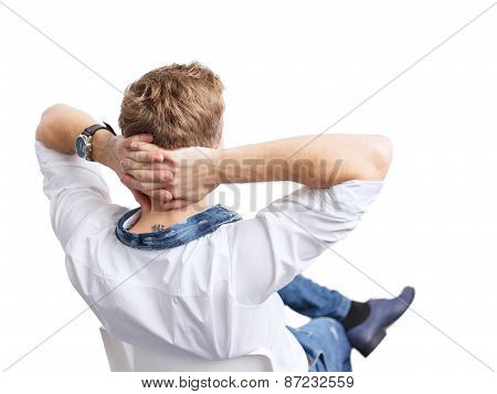 Young relaxed man sitting in chair, view from behind. Isolated on white background.