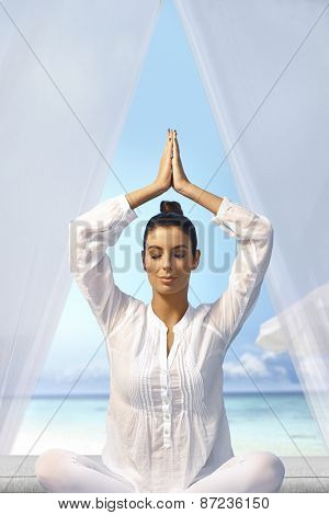 Young woman meditating in prayer position eyes closed on the beach.
