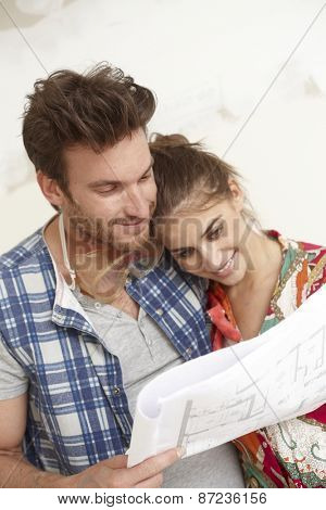 Happy young loving couple planning a new home, looking at floor plan in home under construction.