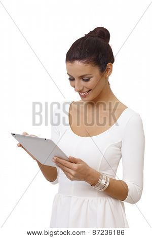 Attractive young woman in white dress using tablet computer, smiling happy.