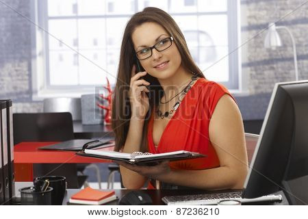 Pretty businesswoman talking on mobilephone, holding personal organizer in office.