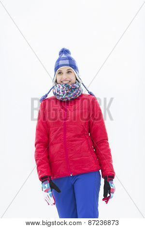 Beautiful young woman in warm clothing walking outdoors