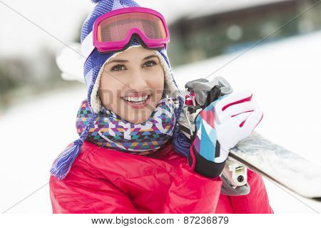 Beautiful young woman carrying skis in snow