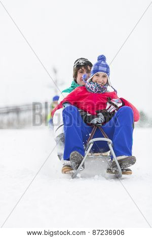 Full length portrait of young couple enjoying sled ride in snow