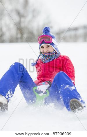 Portrait of happy young woman enjoying sled ride in snow