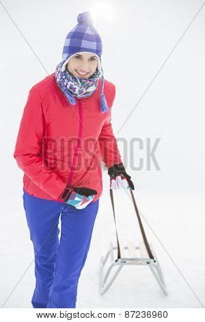 Beautiful young woman pulling sled