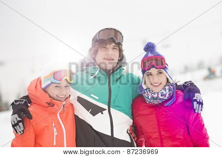 Happy young man with female friends standing arm around in snow