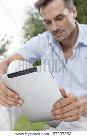Young man using digital tablet in park